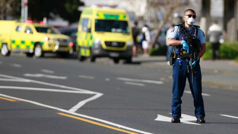 Ein Polizist steht mit Sturmgewehr auf einer Straße, während im Hintergrund gelbe Rettungswagen stehen