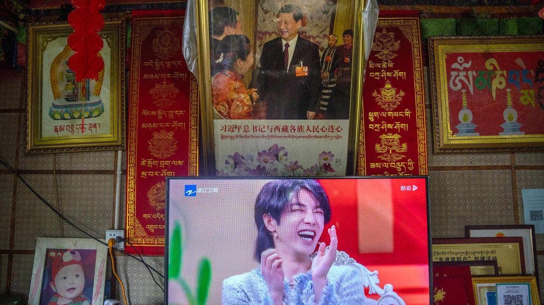 Auf einem TV-Gerät, der in einer Touristenunterkunft unter einem Foto von Staats- und Parteichef Xi steht, ist ein Mann in einer Talkshow zu sehen. Chinas Regierung hat feminin aussehende Männer aus dem Fernsehen verbannt.