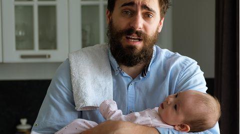 Ein verzweifelter Vater mit einem weinenden Baby