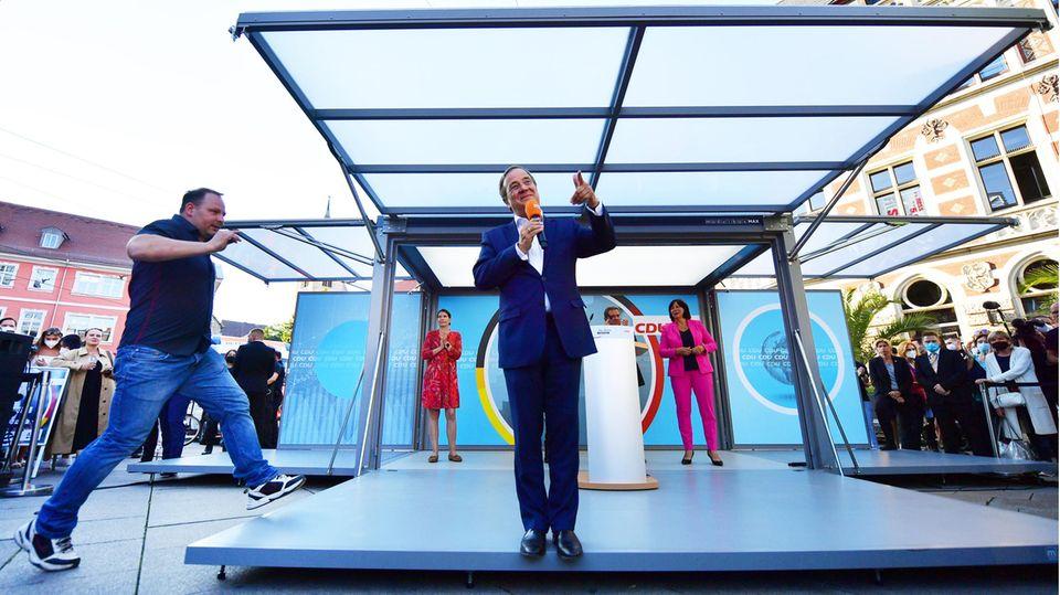 Der Mann springt von links auf die Bühne