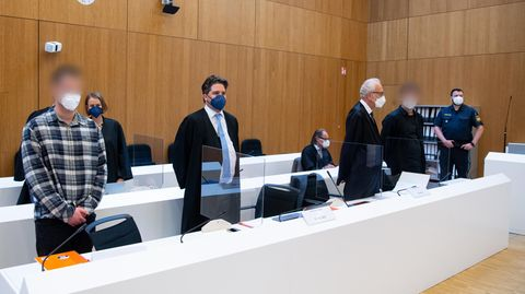 Die zwei wegen Mordes angeklagten Männer (l. und 2.v.r.) stehen mit ihren Anwälten im Sitzungssaal des Landgerichts München (Archivbild)