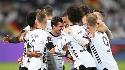 In weißen Trikots und schwarzen Hosen bilden alle zehn Feldspieler des DFB-Teams eine Jubeltraube um den Torschützen