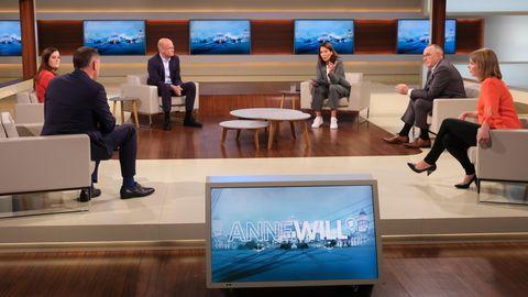 In einem TV-Studio sitzen mit Abstand drei Männer und drei Frauen in Sesseln im Kreis