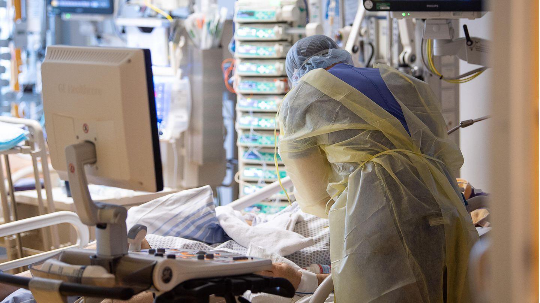 Nierenschäden Corona Studie: Ein Intensivpfleger kümmert sich um einen Covid-19-Patienten