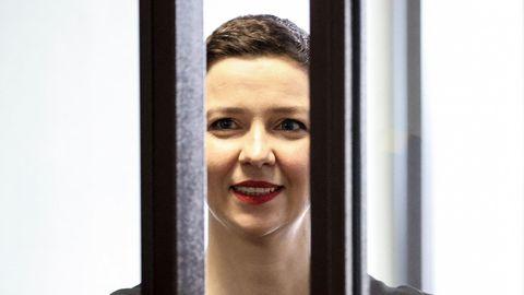 Eine weiße Frau mit kurzen, braunen Haaren lächelt hinter zwei dicken Gitterstäben hervor