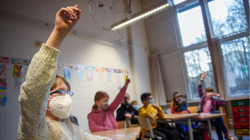 Eine Schülerin einer 4. Klasse hebt im Unterricht an der Grundschule Russee in Kiel die Hand