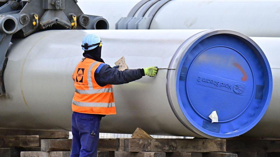 """Ein Mann in blauer Arbeitskleidung und orangener Warnweste misst ein Rohr mit blauem """"Nord Stream 2""""-Verschluss aus"""