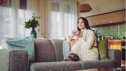 Eine Frau im Strickkleid liegt auf der Couch