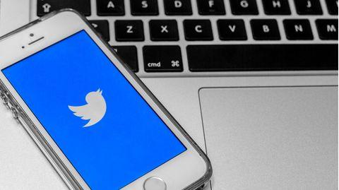 Smartphone mit geöffneter Twitter-App liegt auf einem Laptop.