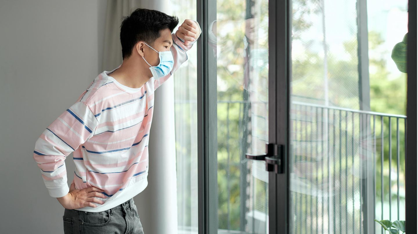 Young Vietnamese stands with mask in front of the window and looks longingly outside.