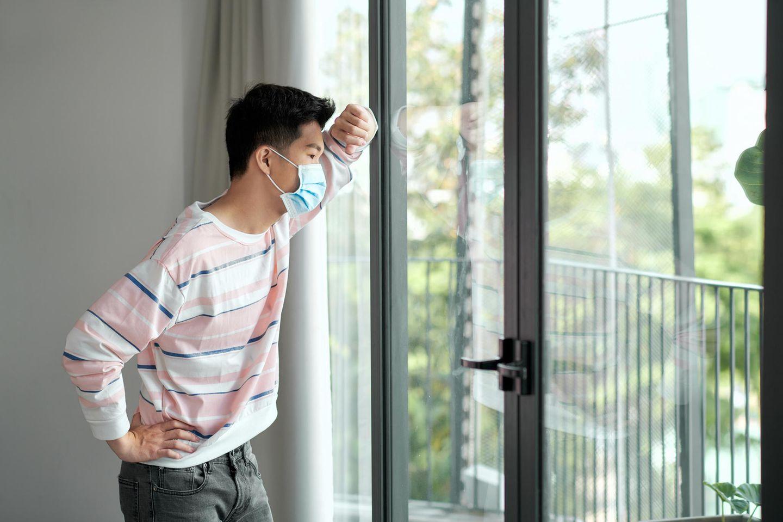Junger Vietnamese steht mit Maske vorm Fenster und schaut sehnsüchtig nach draußen.
