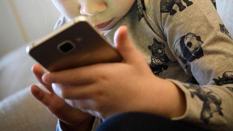 Ein kleines Mädchen schaut auf ein Smartphone
