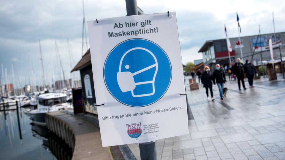 """Ein Schild mit der Aufschrift """"Ab hier gilt Maskenpflicht"""" hängt an der Promenade in Heiligenhafen"""