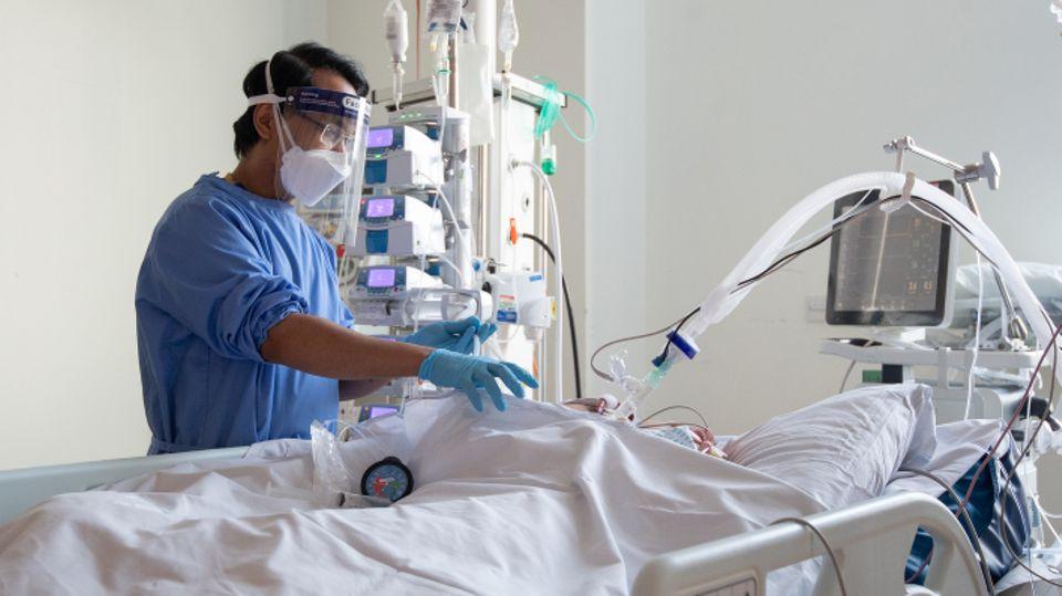 Pflegemitarbeiter kümmern sich auf einer Intensivstationum Patienten mit Covid-19