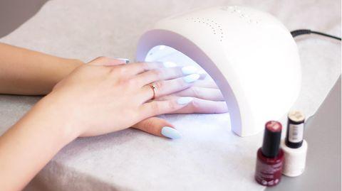 Frau härtet UV-Nagellack unter einem Nagelhärter