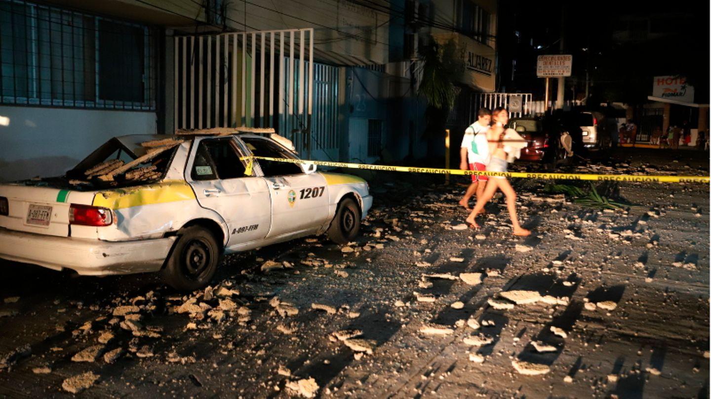 Ein Paar geht an einem Taxi vorbei, das durch herabfallende Trümmer nach einem starken Erdbeben beschädigt wurde.