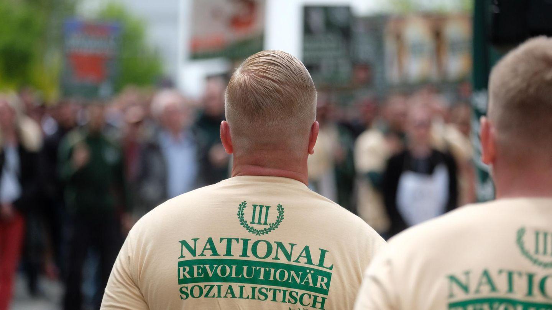 """Zwei weiße, junge Männer mit blonden Haaren und ausrasierten Nacken tragen beige T-Shirts mit dem Logo von """"Der dritte Weg"""""""