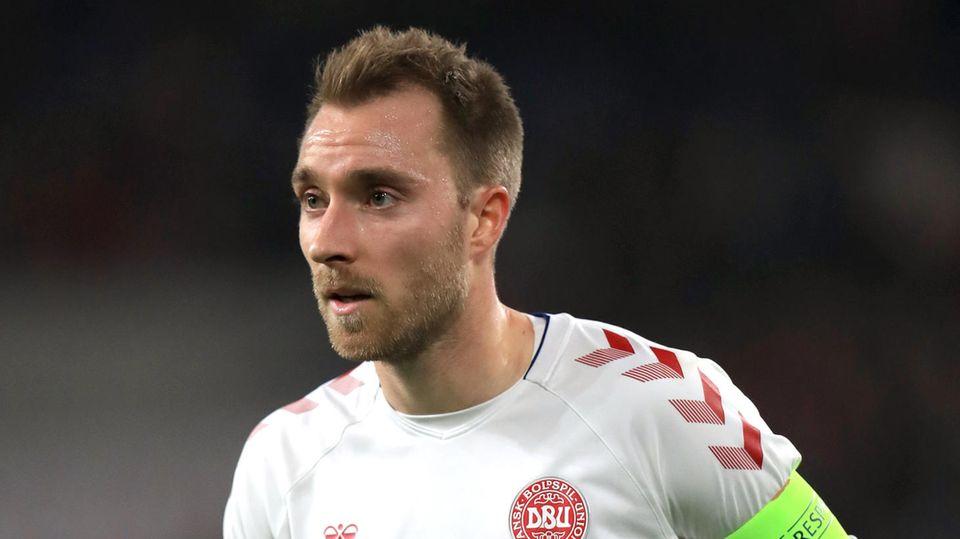 Ein weißer Fußball-Profi mit dunkelblonden Haaren und Drei-Tage-Bart spielt im weiß-roten Trikot des dänischen National-Teams
