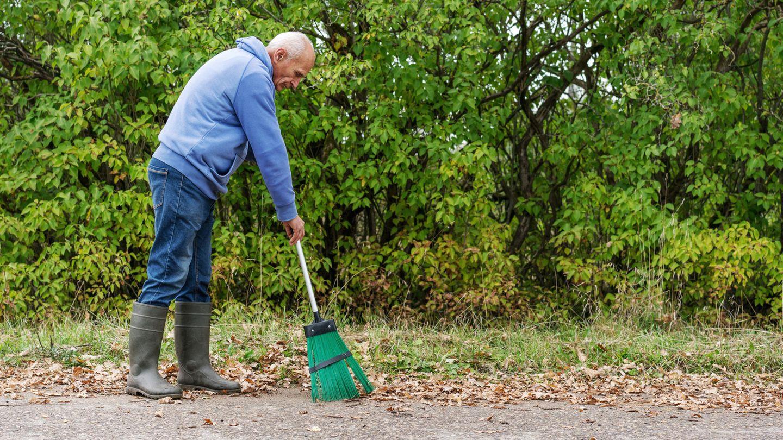 Ein älterer Mann fegt Laub auf der Straße
