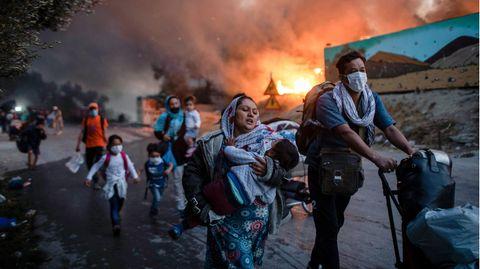 Ein erschütternder Jahrestag:Migranten fliehen am 9. September 2020 vor einem erneuten Feuers mit ihren Habseligkeiten aus dem Flüchtlingslager Moria, nachdem zuvor bereits mehrere Feuer das Lager nahezu vollständig zerstört haben