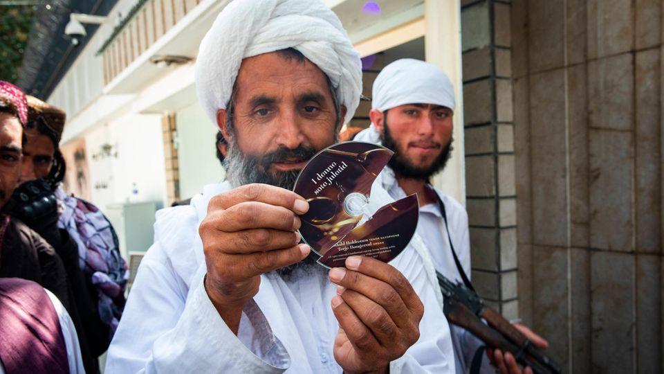 Ein Taliban-Mitglied zeigt eine zerstörte CD mit Weihnachtsmusik