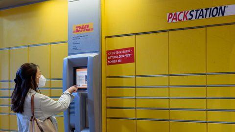 Frau bedient eine Packstation