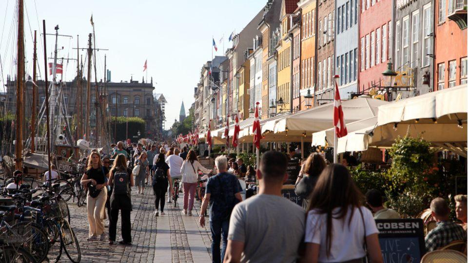 Passanten spazieren am Nyhavn in Kopenhagen entlang, dem bei Touristen beliebten Hafen mit seinen bunten Häuschen.