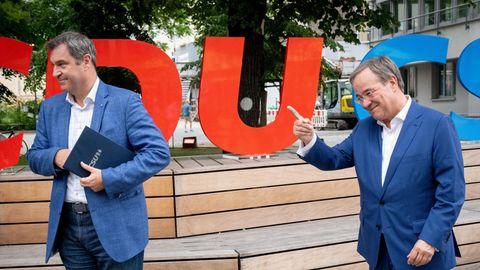 Auf hölzernen Stufen stehen die roten Buchstaben CDU und die blauen Buchstaben CSU, davor zwei weiße Männer in bblauen Anzügen
