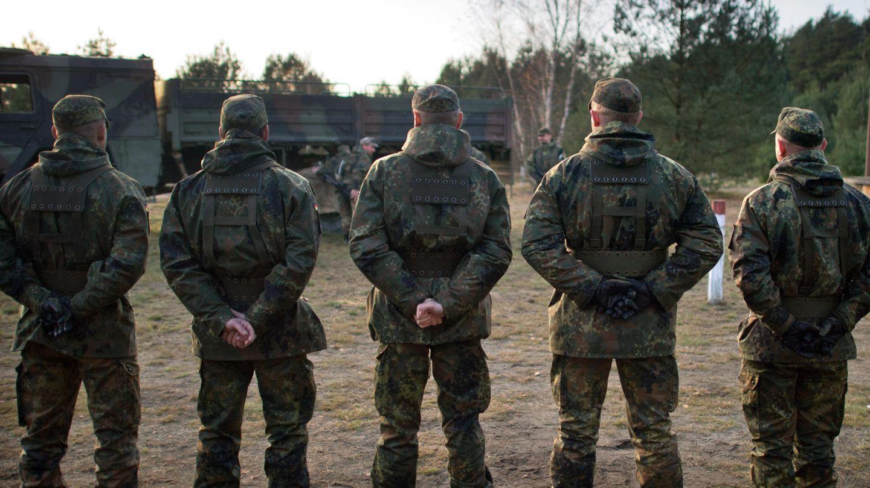 Von hinten sind fünf Bundeswehr-Soldaten zu sehen, die auf einem Truppenübungsplatz in einer Reihe stehen