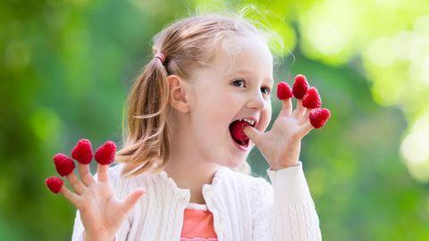 Kleines Mädchen isst Himbeeren