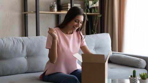 September Deals: Eine Frau öffnet ein Paket und freut sich über den Inhalt.