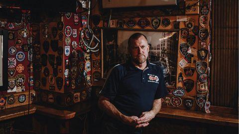 Tim Brown vor den Abzeichen von Feuerwehreinheiten aus dem ganzen Land