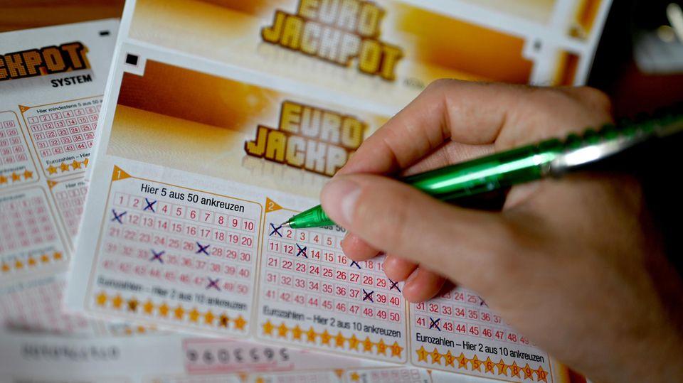 Eine Hand füllt Kästchen für den Eurojackpot aus
