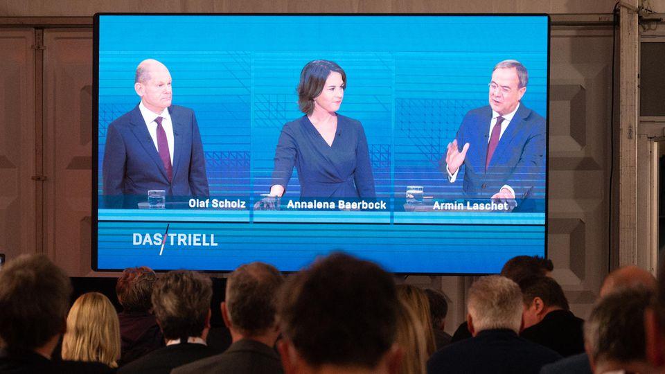 Kanzlerkandidat Olaf Scholz (SPD, l.), Kanzlerkandidatin Annalena Baerbock (Bündnis90/Die Grünen) und Kanzlerkandidat Armin Laschet (CDU) während des Triells auf einem Bildschirm in Berlin.