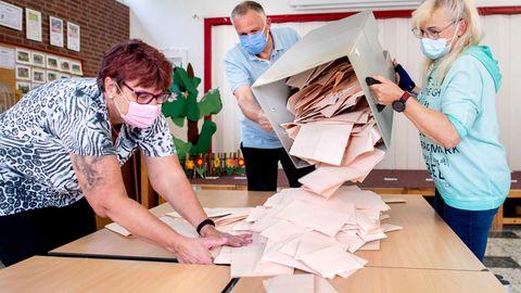 Wahlhelferinnen und ein Wahlhelfer entleeren in einer Grundschule inDelmenhorst eine Wahlurne mit Stimmzetteln