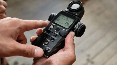 Ein Belichtungsmesser in der Hand eines Fotografen.