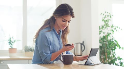 Frau shoppt online auf dem Tablet