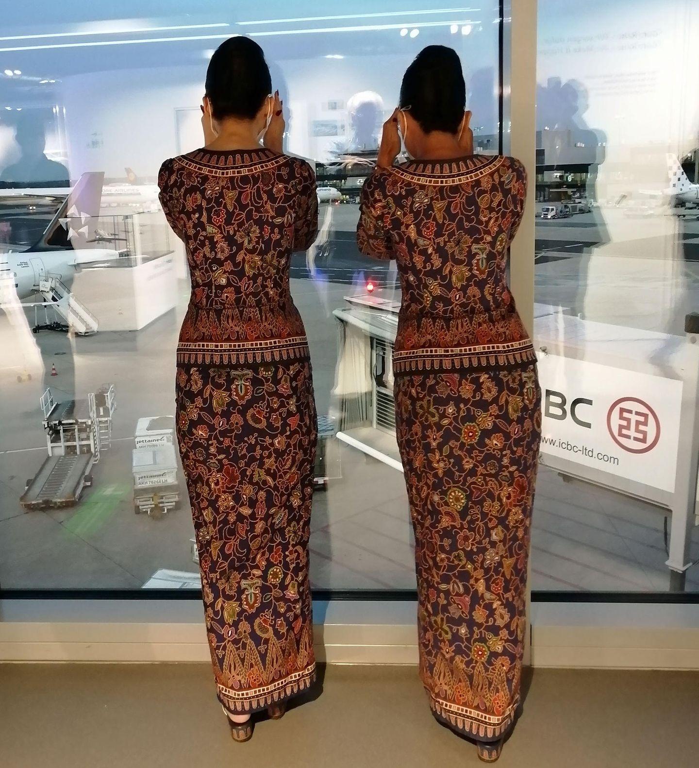 Am Frankfurter Flughafen: Zwei Flugbeleiterinnen beobachten gespannt die Ankunft der Boeing 777 für den Flug nachSingapur.