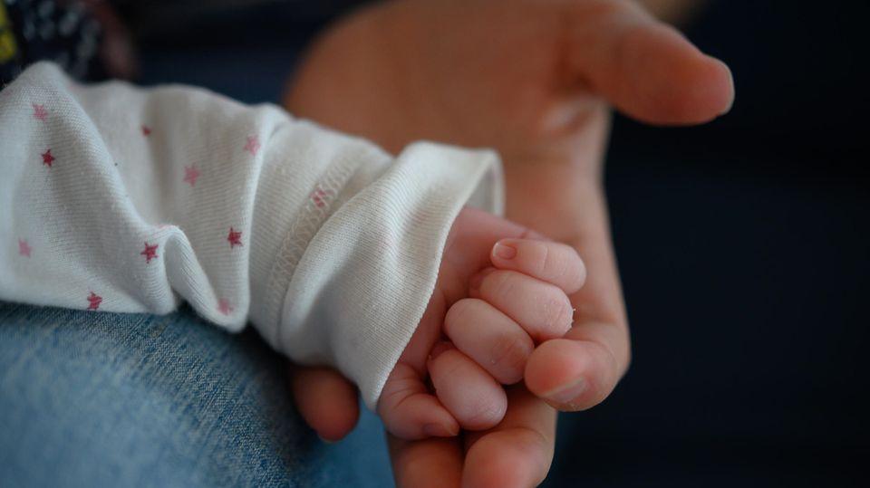 Die Hand eines zwei Wochen alten Neugeborenen liegt in der Hand seiner Mutter