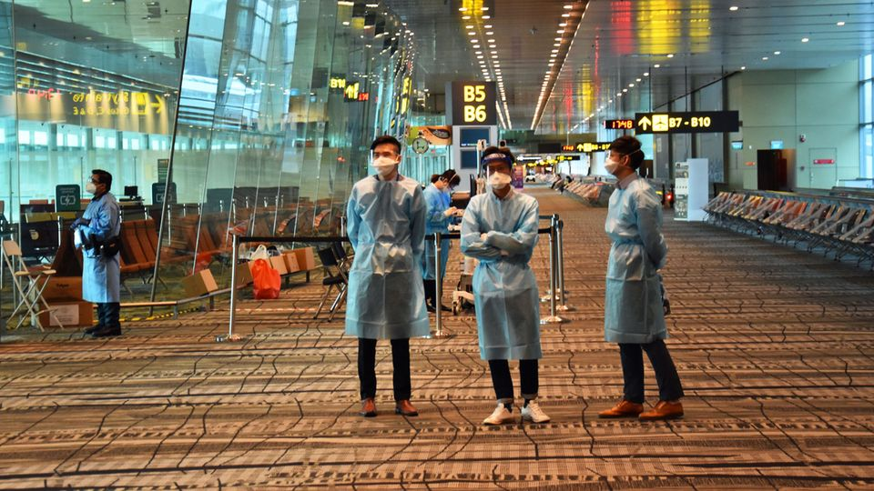 Willkommen als einer von wenigen Flügen in Singapur: Helfendes Flughafenpersonal in Schutzkleidung stehtan jeder Ecke und weist den Weg zum Testzentrum.