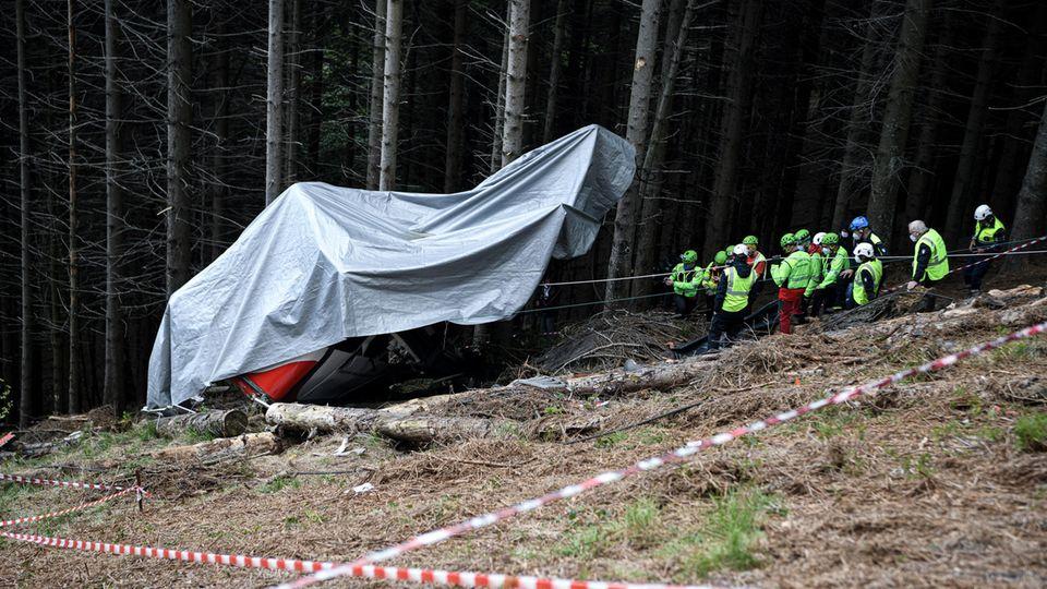 Einsatzkräfte des Bergrettungsdienstes arbeiten nach dem Absturz einer Seilbahngondel an der Unfallstelle