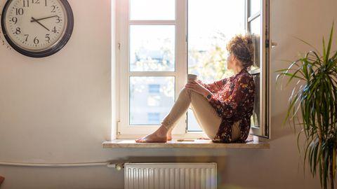 Junge Frau sitzt mit einer Tasse Tee am Fenster und schaut raus