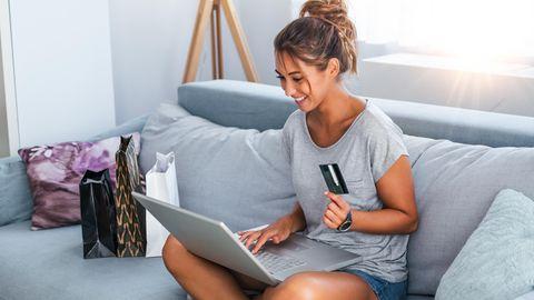 Eine Frau sitzt auf der Couch und bestellt Produkte online.