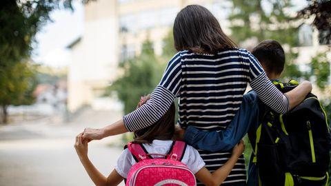 Frau läuft mit zwei Schulkindern im Arm über eine Straße