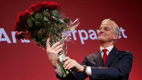 Der Vorsitzende der Arbeiterpartei, Jonas Gahr Støre, hält einen Strauß roter Rosen