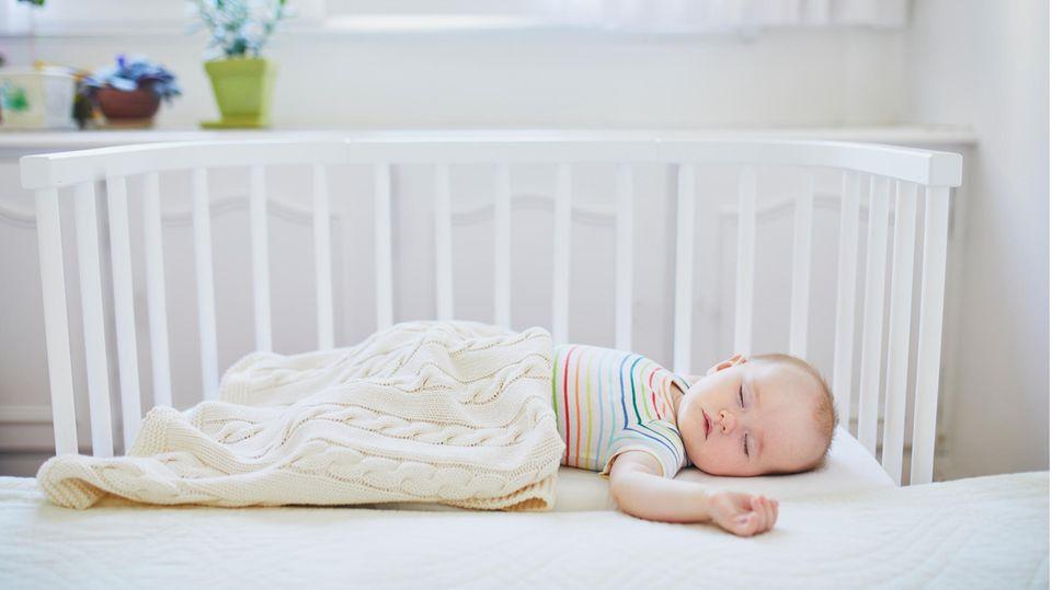 Beistellbetten für Babys: Kleiner Junge schläft zugedeckt in einem weißen Beistellbett
