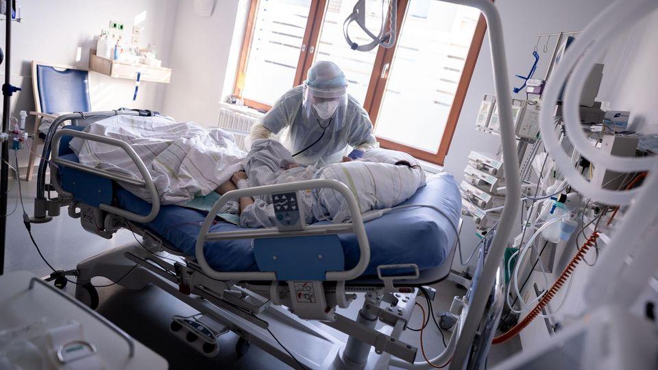 Hospitalisierungsinzidenz RKI: Ein Intensivpfleger kümmert sich um eine an Covid-19 erkrankte Patientin