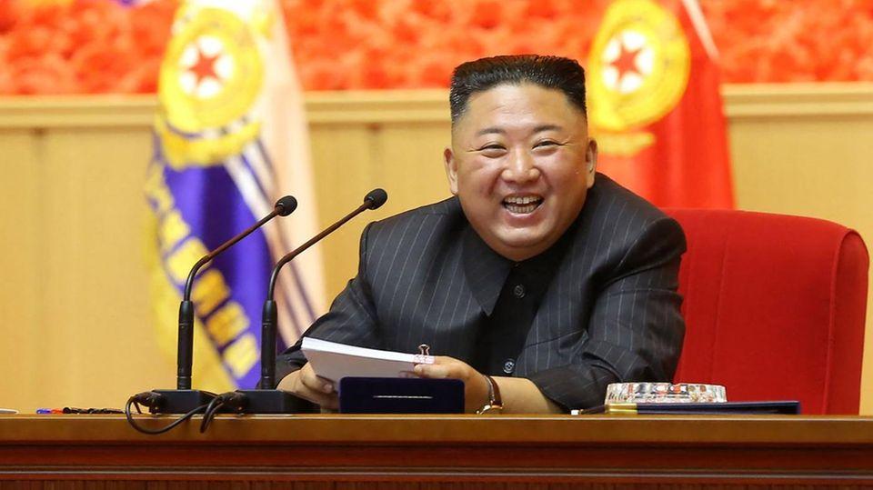 Nordkrieas Diktator Kim Jong Und sitzt an einem Rednerpult und lacht
