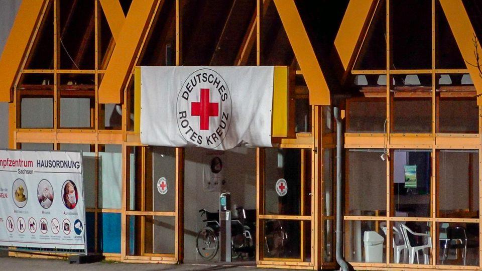 Eine Rot-Kreuz-Fahne hängt über dem Eingang zum Impfzentrum in Eich