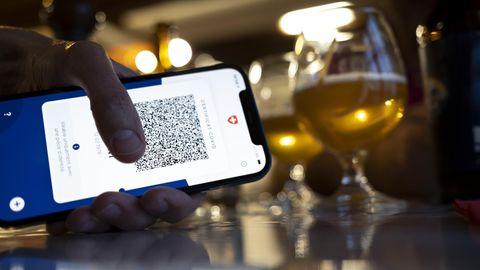 Person hält ein Smartphone mit Corona-Zertifikat, im Hintergrund zwei Biergläser